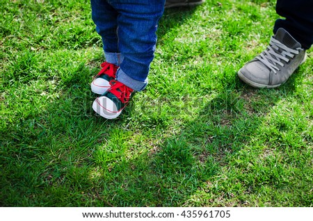 First steps concept - foot of father and son in stylish sneakers on the background of green grass. Father's Day. Happy Fathers Day. Happy family. Father and baby. Copy space.