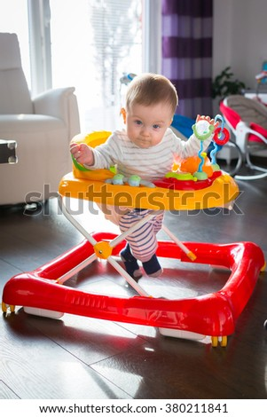 First steps in the baby walker by little baby boy - stock photo
