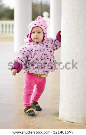first steps of baby girl outdoors - stock photo