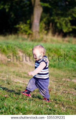First steps of baby on nature background - stock photo