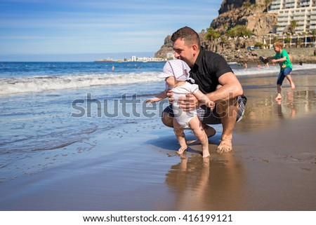 First steps of little baby girl with her father at the beach