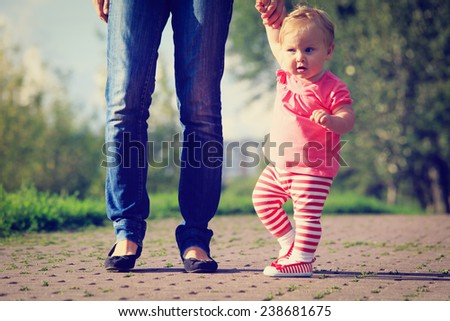 first steps of little girl in summer park - stock photo