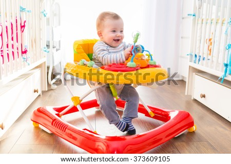 First steps of the boy in a baby walker - stock photo