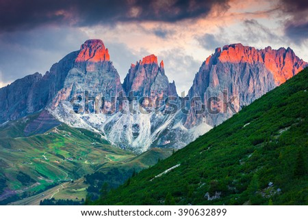 First sunlight glowing the tops of spiers of Plattkofel and Langkofel mountain ranges. Sunrise in Dolomite Alps. View from Pordoi pass, Province of Bolzano - South Tyrol, Italy, Europe.