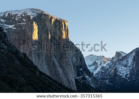 First sunlight streaking across El Capitan during a winter sunrise.  Snow capped Clouds Rest and Half Dome are also visible. - stock photo