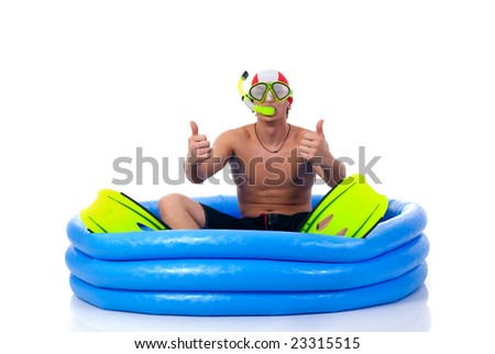 First swimming lessons for dummies, young man with snorkel, goggles and flippers.  Humorous studio shot. - stock photo