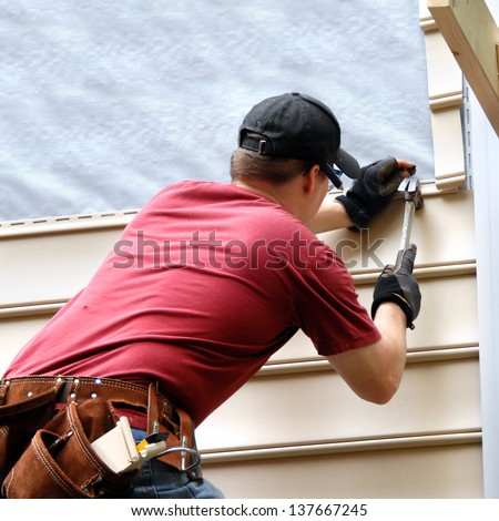 First time home buyer works to install siding on his new home.  He is hammering into place a sheet of siding.  He has on a red shirt and is holding hammer and nail. - stock photo