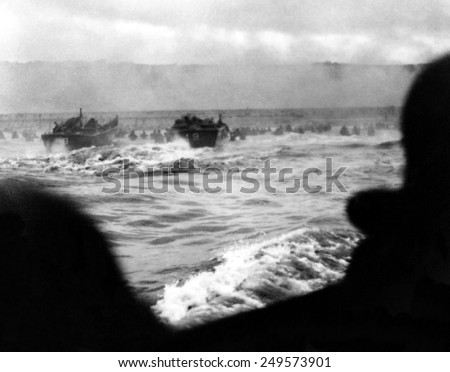 First wave of U.S. invasion troops approach Omaha beach during the D-Day invasion of Normandy. Smoke screen in the distance and soldiers advance under fire with water up to the waist. June 6, 1944 - stock photo