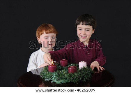 First Week of Advent: Two brothers light an Advent wreath to prepare for Christmas - stock photo