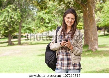 First-year student using a smartphone in a park - stock photo