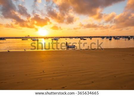 Fiserman with boat in the ocean near the sandy beach on the sunrise - stock photo