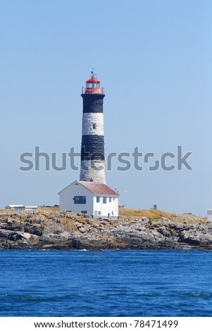 Fisgard Lighthouse in Victoria - BC, Canada Lighthouses are used to mark dangerous coastlines, hazardous shoals and reefs, and safe entries to harbors, and can also assist in aerial navigation. - stock photo