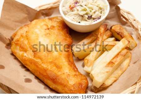 fish and chips, a classic diner meal. This fresh haddock fillet is coated with batter and deep fried with home made french fries and coleslaw. - stock photo
