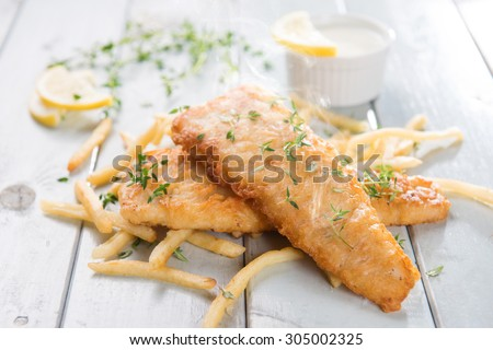 Fish and chips. Fried fish fillet with french fries on bright wooden background. Fresh cooked with hot smoke. - stock photo