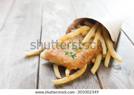 Fish and chips. Fried fish fillet with french fries wrapped by paper cone, on wooden background. - stock photo