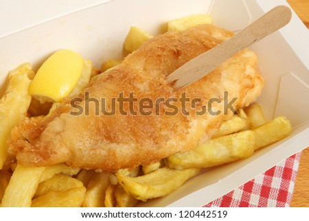 Fish and chips in takeaway carton. - stock photo