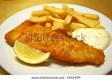 Fish and chips on a white plate with tartar sauce - stock photo