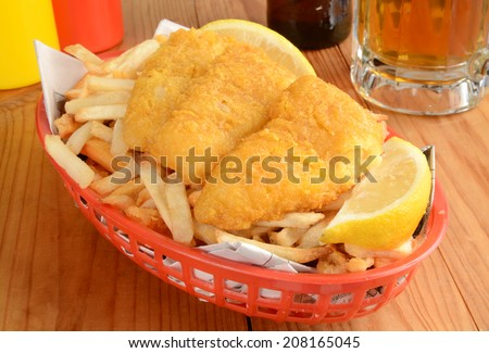 Fish and chips served in a basket wrapped in newsprint with a mug of beer