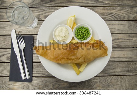 Fish and chips served with tartar sauce, green peas and lemon on a rustic background - stock photo