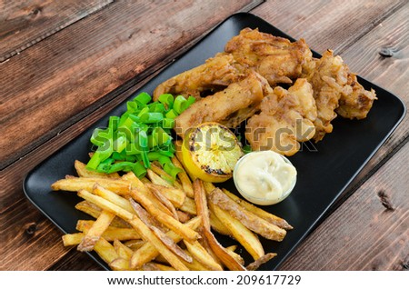 Fish and chips with homemade mayonnaise on black plate