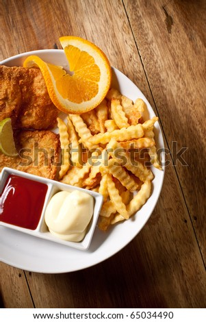Fish and chips with ketchup and mayonnaise, decorated with lemon.