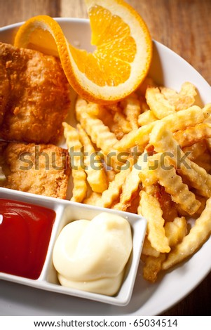 Fish and chips with ketchup and mayonnaise, decorated with lemon. - stock photo
