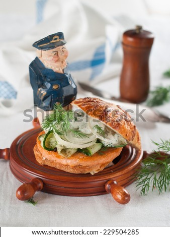 Fish and crab burgers on wooden serving plate, selective focus - stock photo