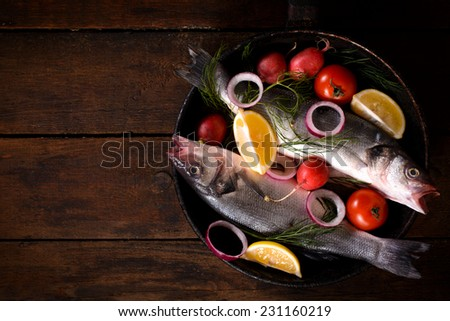 Fish and ingredients in pan on the wooden background with blank space - stock photo