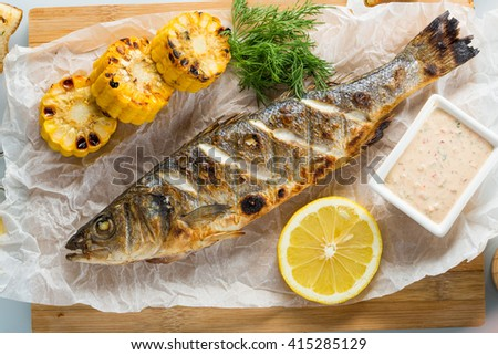 fish baked on the grill. with potatoes and lemon.  - stock photo