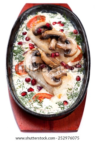 Fish baked with vegetables and mushrooms - stock photo