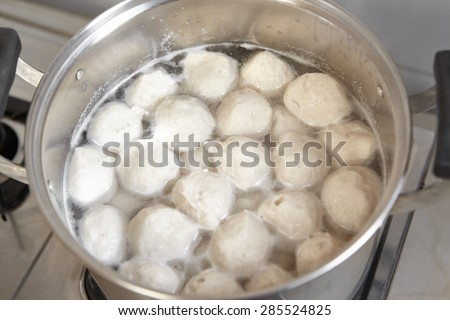 Fish ball on the boiled water inside the pan - stock photo