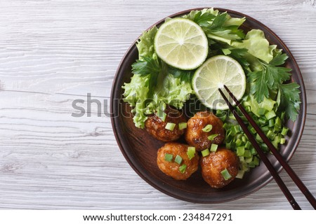Fish balls in curry sauce on a plate with fresh herbs. top view of a horizontal  - stock photo