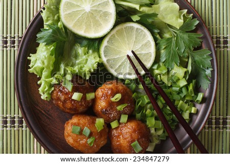 fish balls in curry sauce with lime and fresh herbs and chopsticks on a bamboo table close-up. horizontal view from above  - stock photo