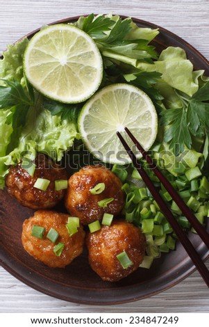 Fish balls with fresh herbs and chopsticks close-up. top view of the vertical  - stock photo