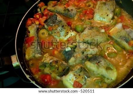 Fish being cooked in a delicious herb and vegetable sauce