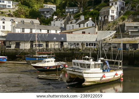 fish-boats aground at harbor, Polperro, cityscape of the touristic village on southern coast of Cornwall with low tide in the river harbor and old fish-boats aground