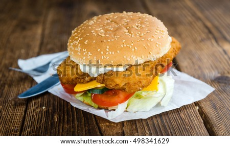 Fish Burger (selective focus; close-up shot) on wooden background