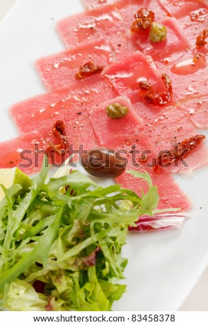 Fish Carpaccio with olives ana salad - stock photo