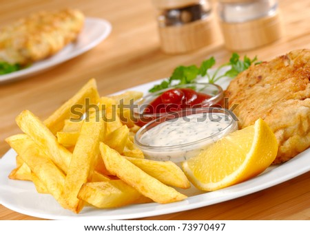 Fish, chips, mayo and ketchup on the white plate - stock photo