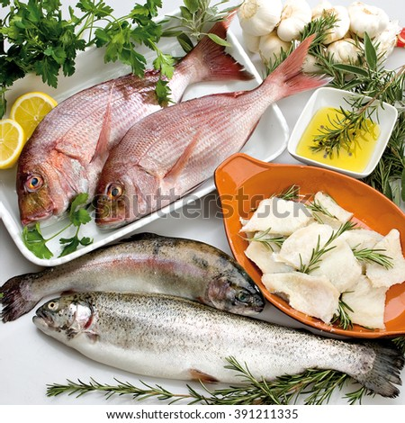 Fish composition with vegetables, garlic, rosemary and parsley with oil, trout, snapper and cod - stock photo
