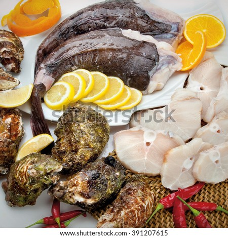 Fish composition with vegetables, onions, salad and red pepper, monkfish, swordfish and oysters seafood - stock photo