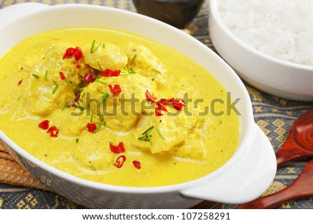 Fish cooked in spicy coconut sauce, garnished with chilli and chives,  and served with basmati rice. - stock photo
