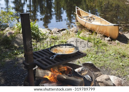 Fish cooking in a frying pan over an open fire with a canoe and northern Minnesota lake in the background - stock photo