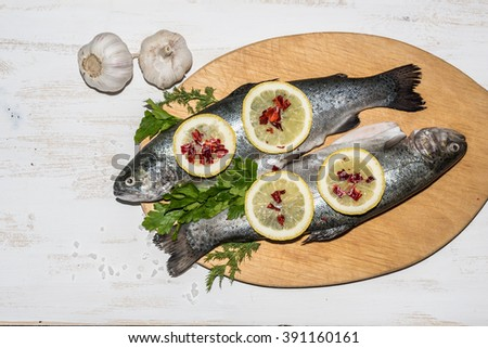 Fish dish cooking with various ingredients. Raw rainbow trout with lemon, garlic ,herbs and spices on cutting board , top view. Healthy food or diet nutrition concept. - stock photo