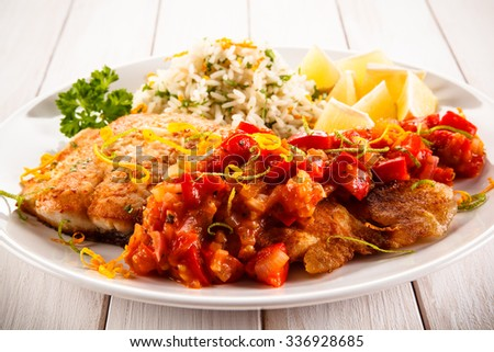 Fish dish - fried fish fillet white rice and vegetables  - stock photo