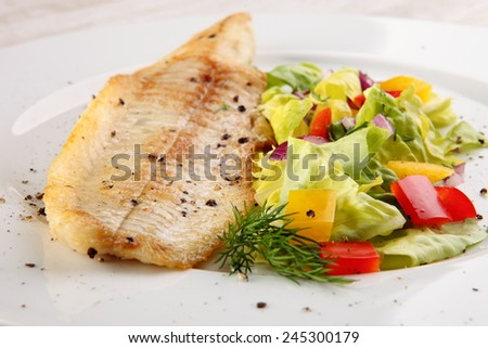 Fish dish - fried fish, fried potatoes and vegetables  - stock photo