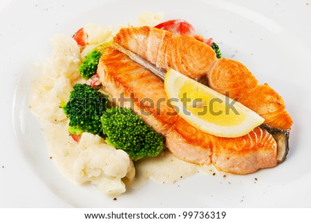 Fish dish - grilled salmon with cauliflower, broccoli and lemon slice on plate - stock photo