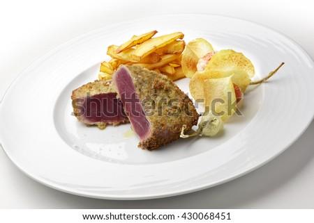 Fish dish portion escalope bluefin tuna breading capers and potatoes - stock photo