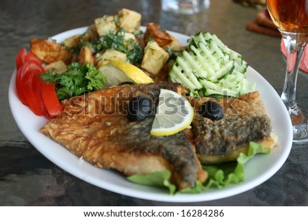 Fish dish with vegetables .