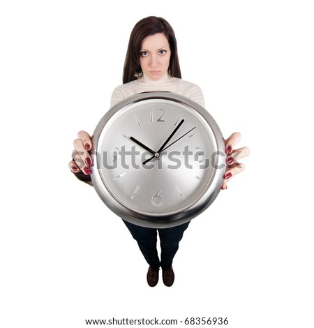 Fish eye view of a girl holding a clock with both hands and looking at camera - the clock seems huge. - stock photo